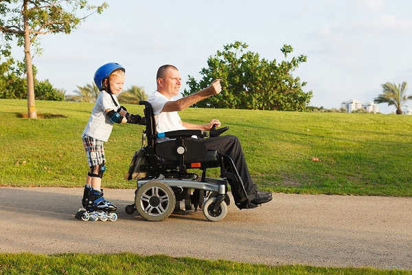 Man with ALS in a wheelchair enjoys an afternoon with his son who is rollerblading