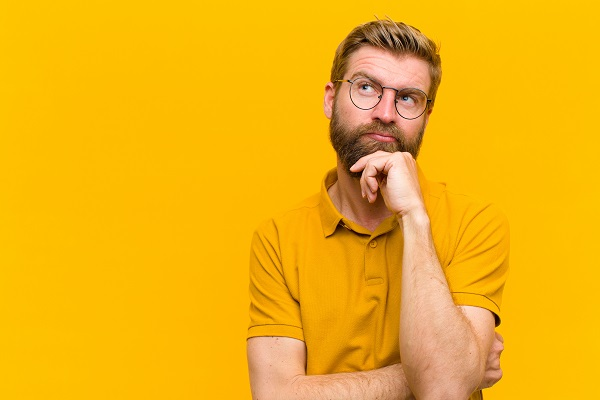 Man with glasses in a yellow shirt in front of a yellow background holding his chin and looking upward as if wondering about something