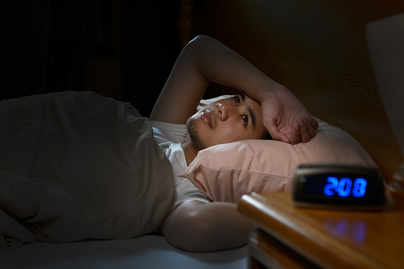 A young man is lying awake in bed unable to sleep with a clock showing 2am in the foreground