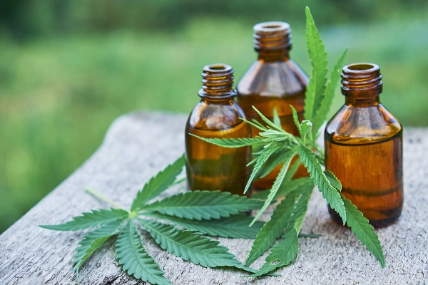 Brown bottles of marijuana tinctures with cannabis leaves on a wooden table outdoors