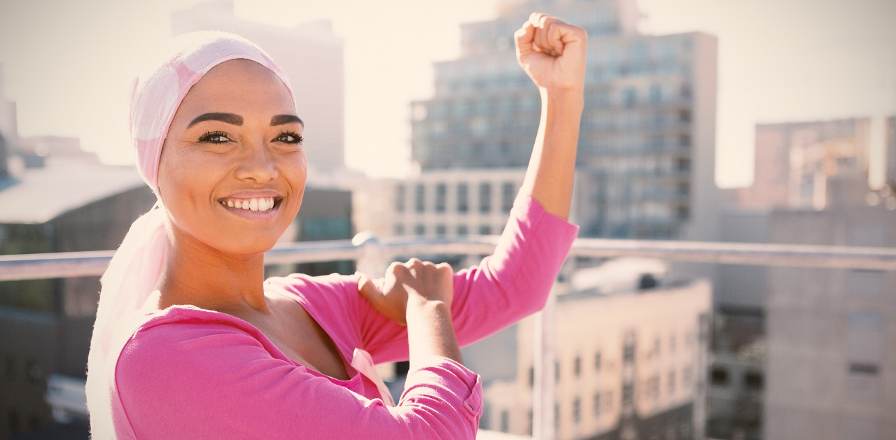 Young woman on a rooftop with the city in the background wearing pink and a head covering and flexing her arm to show fight against cancer