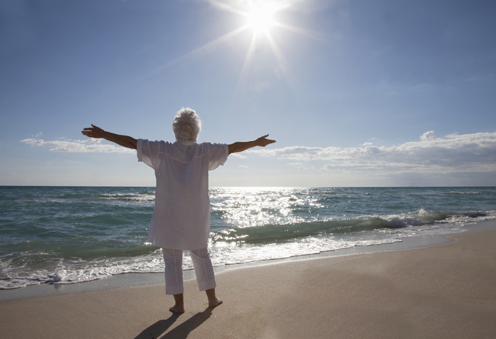 An older woman stands on the beach and holds her arms open wide to the sunshine